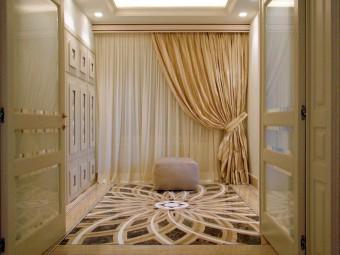 INGRESSO. Pavimento realizzato in marmo con gli intarsi decorativi. Controsoffitto con illuminazione integrata. Porte tailor made (BEZUS - AGOSTINI). Pouf rivestito in camoscio (BAXTER).