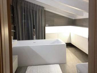 BAGNO PADRONALE. Soffitto con travi a vista. Pavimento e rivestimento in gres porcellanato. Arredamento personalizzato con illuminazione incorporata (BEZUS - LPL).