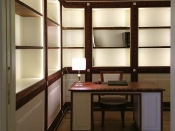 LIBRERIA realizzata in combinazione di due materiali: essenza di Palissandro Santos e legno laccato opaco, composta da ripiani spostabili e vani con ante, illuminata con luci LED.